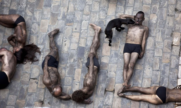 "Animal rights protesters lie covered in black paint as they form the words ""Stop bullfighting"" during a demonstration calling for the abolition of bull runs and bullfights, a day before the start of the famous running of the bulls San Fermin festival in Pamplona July 5, 2012. (Susana Vera/Reuters)"