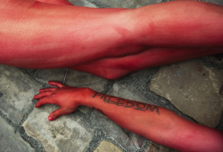 """Animal rights protesters lie covered in fake blood as they form the words """"Stop bullfighting"""" during a demonstration calling for the abolition of bull runs and bullfights, a day before the start of the famous running of the bulls San Fermin festival, in Pamplona July 5, 2012. (Susana Vera/Reuters)"""