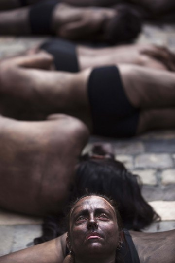 """Animal rights protesters lie covered in black paint as they form the words """"Stop bullfighting"""" during a demonstration calling for the abolition of bull runs and bullfights, a day before the start of the famous running of the bulls San Fermin festival in Pamplona July 5, 2012. (Susana Vera/Reuters)"""