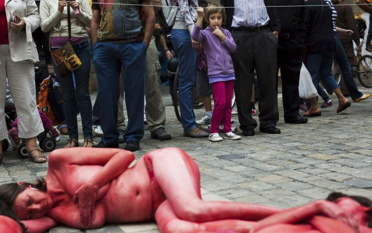 """A girl looks at animal rights protesters as they lie covered in fake blood and black paint while forming the words """"Stop bullfighting"""" during a demonstration calling for the abolition of bull runs and bullfights, a day before the start of the famous running of the bulls San Fermin festival in Pamplona July 5, 2012. (Susana Vera/Reuters)"""