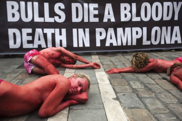 "Animal rights protesters lie covered in fake blood as they form the words ""Stop bullfighting"" during a demonstration calling for the abolition of bull runs and bullfights, a day before the start of the famous running of the bulls San Fermin festival, in Pamplona July 5, 2012. (Susana Vera/Reuters)"