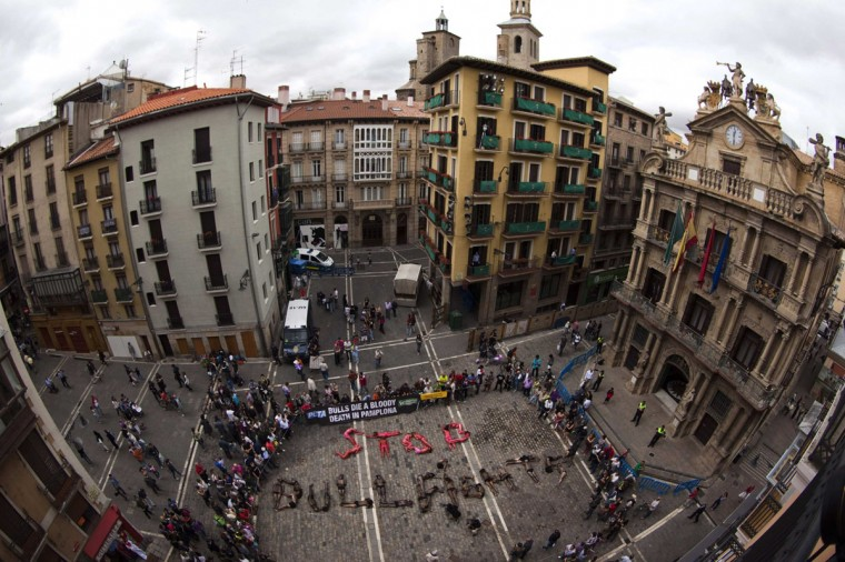 "Animal rights protesters lie covered in fake blood and black paint as they form the words ""Stop bullfighting"" during a demonstration calling for the abolition of bull runs and bullfights, a day before the start of the famous running of the bulls San Fermin festival, in Pamplona July 5, 2012. (Susana Vera/Reuters)"