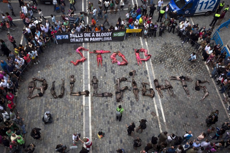 "Animal rights protesters lie covered in fake blood and black paint as they form the words ""Stop bullfighting"" during a demonstration calling for the abolition of bull runs and bullfights, a day before the start of the famous running of the bulls San Fermin festival, in Pamplona July 5, 2012. The annual week-long fiesta gets underway July 6, with the first bull run in the morning of July 7. (Susana Vera/Reuters)"