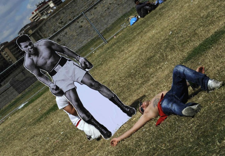 A reveller sleeps next to a cardboard cutout of U.S. boxer Muhammad Ali in the Ciudadela Park at the San Fermin festival in Pamplona July 8, 2012. The cutout is part of a creative campaign by a publicity agency. (Eloy Alonso/Reuters)