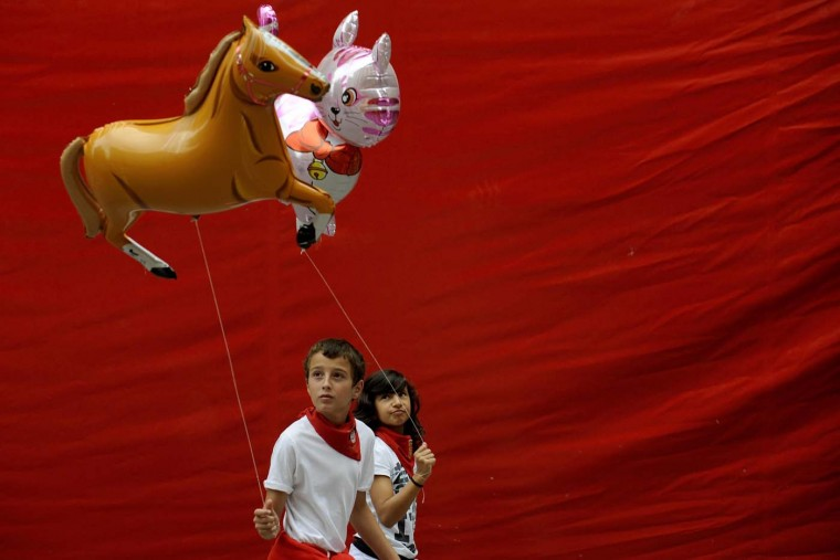 Children carrying balloons walk past a red tarpaulin on the fourth day of the San Fermin festival in Pamplona July 9, 2012. (Eloy Alonso/Reuters)