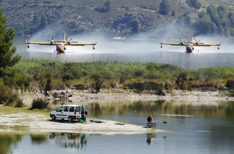 Firefighting planes fetch water from the Beniares reservoir to fight a wildfire next to the Sierra Mariola Nature Park in Cocentaina near Alicante, Spain. (Heino Kalis/Reuters)