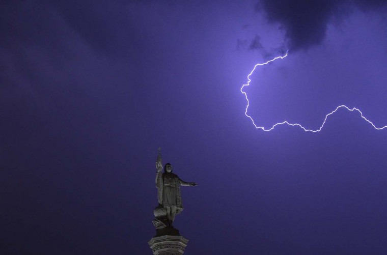 Lightning is seen in the sky above the Christopher Columbus monument at Madrid's Colon Square July 26, 2012. (Juan Medina/Reuters)