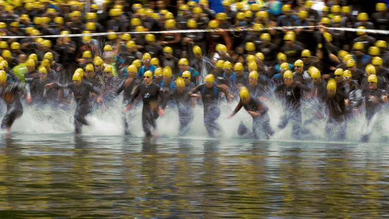 Athletes race into the waters of Lake Zurich for the start of the swimming leg of the Ironman Switzerland Triathlon in Zurich. (Arnd Wiegmann/Reuters)