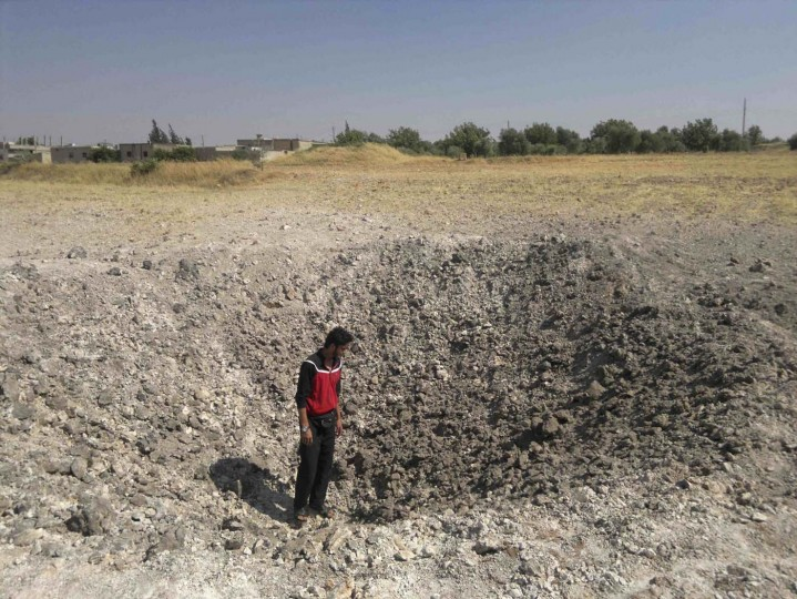 A man stands in a crater, which anti-government activists say was caused by a bomb by pro-government forces, at al-Zapharaneh near Homs July 7, 2012.(Shaam News Network/Reuters Handout)