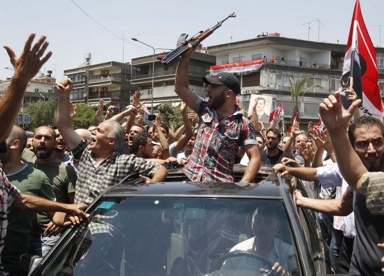 Mourners gather around a car carrying the coffin of the late Syrian Defense Minister Daoud Rajha during his funeral in Damascus July 20, 2012. Rajha was killed by a bomb, which exploded during a meeting of ministers and security officials at a national security building in Damascus two days ago. (Khaled al-Hariri/Reuters)