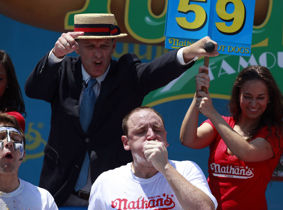 Joey Chestnut (C) competes in the 2012 Nathan's Famous Fourth of July International Eating Contest at Coney Island in the Brooklyn borough of New York. Chestnut ate a record-tying 68 hot dogs to take the crown. (Eric Thayer, Reuters photo)