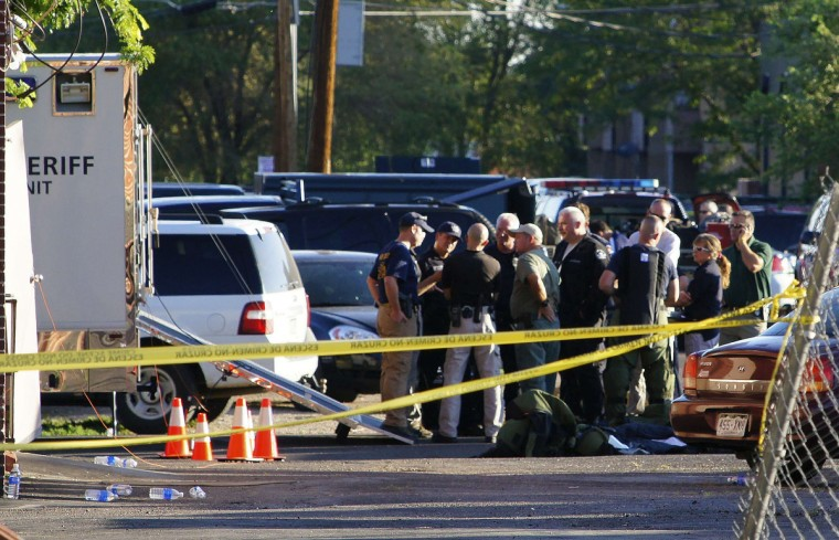 FBI officers, Aurora police officers, and fire crews are pictured outside the Denver shooting suspect's apartment building in Aurora Colorado. (Jason Hatfield/Reuters photo)