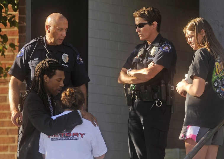 People react outside Gateway High School a few blocks from the scene of the Century 16 Theatre shootings in Aurora, Colorado. (Evan Semon/Reuters photo)