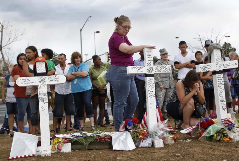 People pay their respects at a memorial for victims behind the theater where a gunman opened fire on moviegoers in Aurora, Colorado. President Barack Obama travels to Colorado on Sunday to meet families bereaved after a gunman went on a shooting rampage at a movie theater in a Denver suburb. (Shannon Stapleton/Reuters photo)