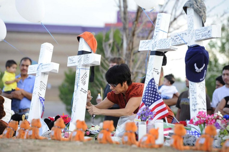 Annette Lucero writes on a cross with a marker at the memorial site for the people killed by a gunman last Friday in the Century 16 movie theater in Aurora, Colorado. Residents of a Denver suburb mourned their dead on Sunday from a shooting rampage by a gunman. (Jeremy Papasso/Reuters photo)