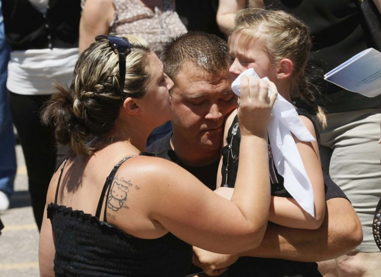 "Amber Vigil (L) consoles Kailyn Vigil, second cousin of massacre victim Micayla Medek, after her funeral in Aurora July 26, 2012. Family and friends filed into a Denver church on Thursday for the funeral of the 23-year-old woman who was among the 12 people killed in a massacre at the opening of the new ""Batman"" movie. (Rick Wilking/Reuters)"
