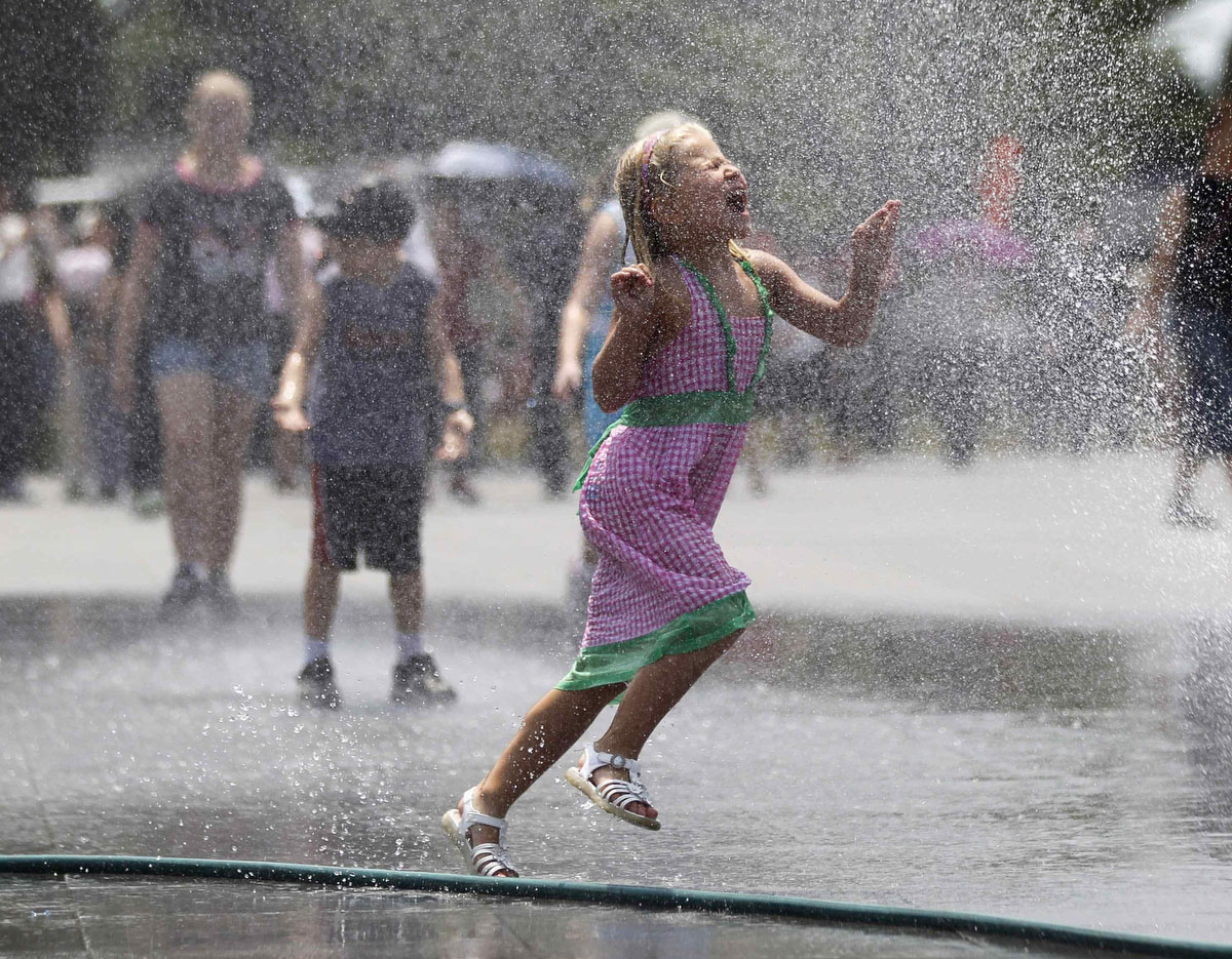 A girl runs through a spray of water leaking from a hose outside the Lincoln Memorial on the Washington Mall. Temperatures in the nation's capital hovered around 100 degrees (38 celcius) again on Thursday along the mid-Atlantic Coast. About 600,000 customers from Ohio to Virginia remained without power, six days after violent storms first struck and as a heat wave continues to bake much of the region, local power companies said Thursday. (Jason Reed/Reuters)