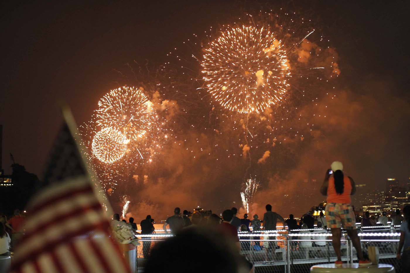 HOBOKEN, NJ - JULY 04: People look at fireworks exploding over the Hudson River and the skyline of New York during the Macy's Independence Day celebration as seen from Hoboken, New Jersey. (Eduardo Munoz/Reuters)