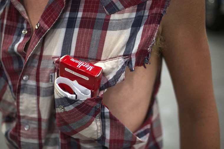 A young truck driver carries a pack of Marlboro cigarettes in the front pocket of a torn shirt during the Iowa 80 truck stop's 33rd Annual Truckers Jamboree in Walcott, Iowa on July 12, 2012. The Iowa 80, located along Interstate 80, is said to be the world's largest truck stop. (Adrees Latif/Reuters)