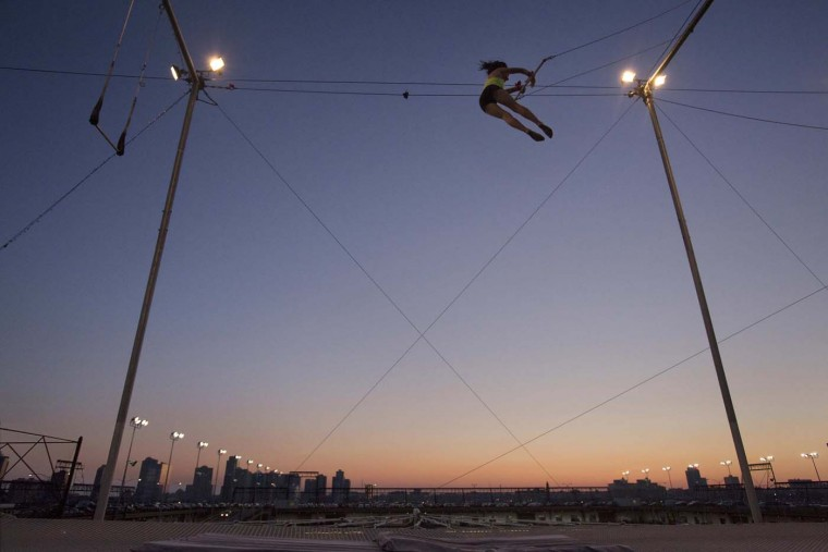A woman practices on a trapeze shortly after sunset at the Trapeze School in New York. At the school, students learn trapeze maneuvers with the skyscrapers of Lower Manhattan as a backdrop. Picture taken July 1, 2012. (Lee Celano/Reuters)