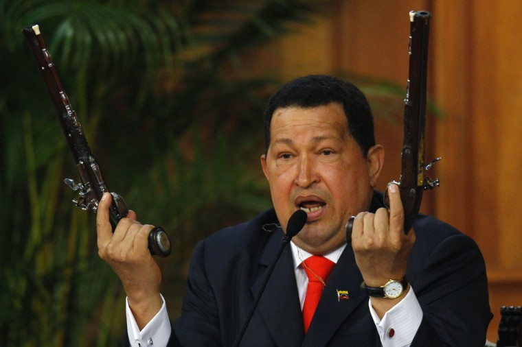 Venezuelan President Hugo Chavez shows the pistols of independence hero Simon Bolivar during a ceremony to mark the his birthday in Caracas. Chavez unveiled a 3D image of South America's 19th century independence hero Bolivar on Tuesday, based on bones he had exhumed two years ago to test a theory that Bolivar was murdered. (Carlos Garcia Rawlins/Reuters)