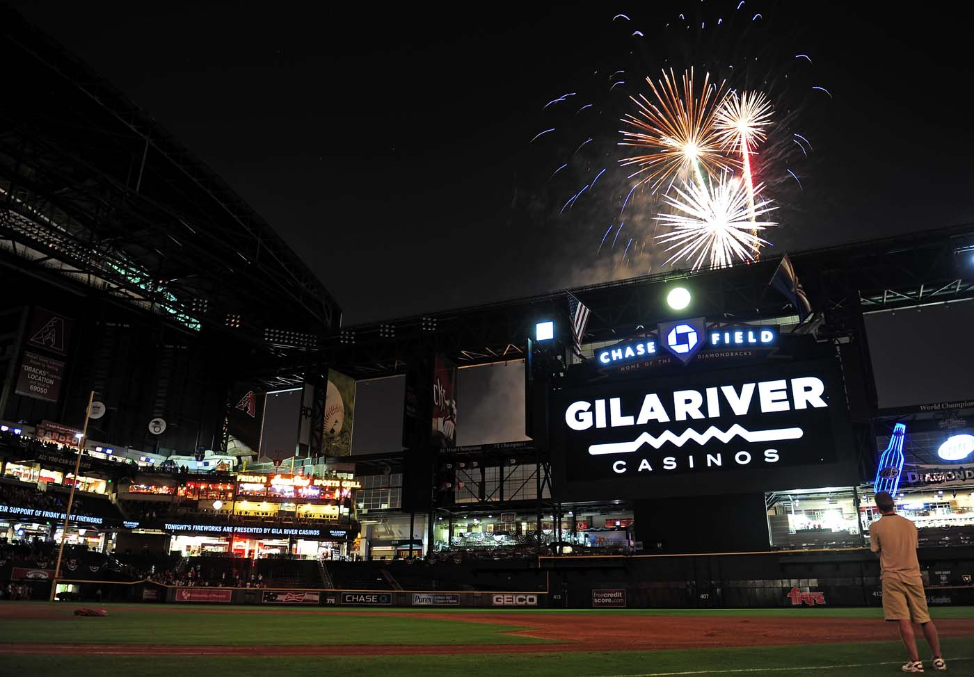PHOENIX, AZ - JULY 04: Fans sit on the field and watch a fireworks show after the game between Arizona Diamondbacks and San Diego Padres at Chase Field. (Jennifer Stewart/US Presswire)