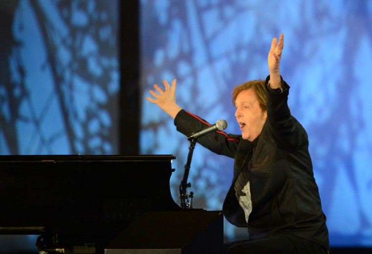 British musician Paul McCartney raises his arms as he sings at the end of the opening ceremony of the London 2012 Olympic Games. (Cristophe Simon/AFP/Getty Images)