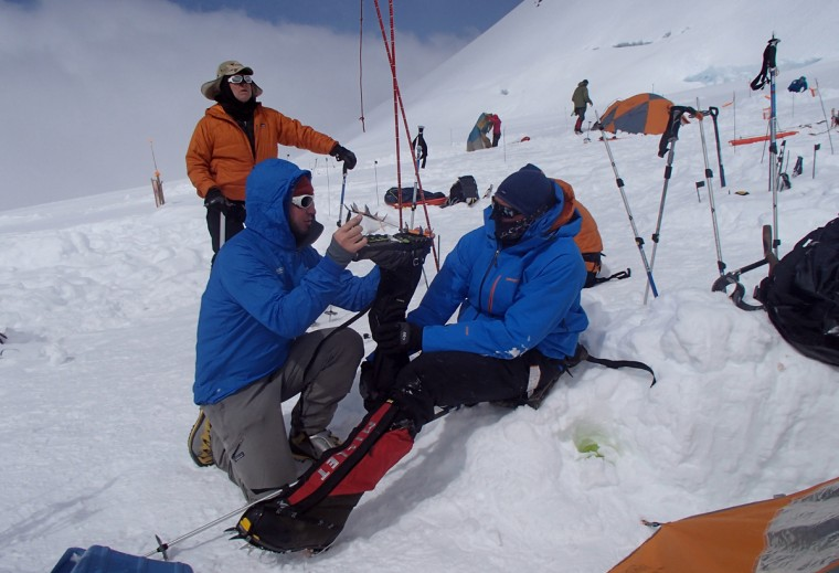 Kirk Bauer (back left) waits while Mountain Trip guide Gabi Benel helps Dave Bordon with the boots on his prosthetic leg. (Disabled Sports USA - Warfighter Sports)
