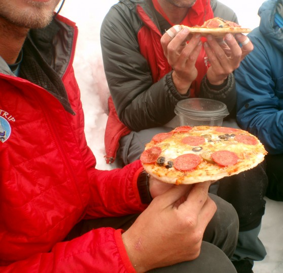 The group stops for a slice of frozen pizza. Food was often stored in the snow and exchanged with other groups for food and fuel, Kirk Bauer said. (Disabled Sports USA - Warfighter Sports)