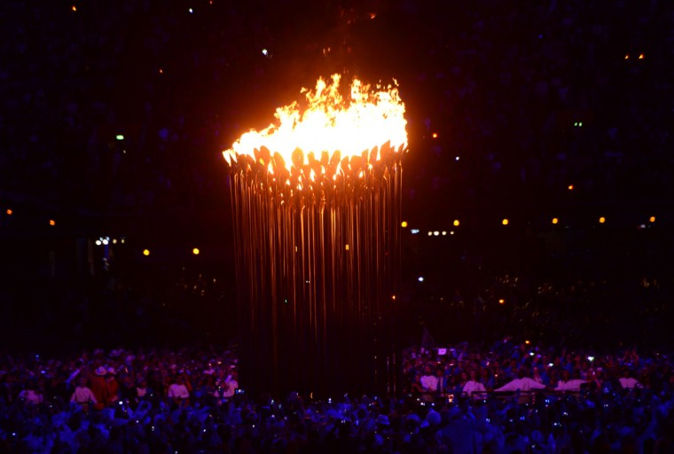 People gather around the Olympic flame after the cauldron in the Olympic Stadium is lit during the opening ceremony. (Christophe Simon/AFP/Getty Images)