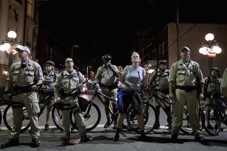 A protester (C) dances next to police officers at the Republican National Convention in Tampa, Florida early August 28, 2012. REUTERS/Philip Andrews/Reuters)