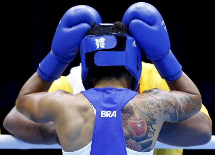 Brazil's Adriana Araujo adjusts her headgear before the quarterfinal Women's Light (60kg) boxing match against Morocco's Mahjouba Oubtil at the London Olympic Games August 6, 2012. (Murad Sezer/Reuters)