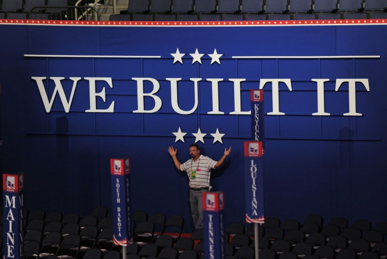 A man poses underneath the day's slogan at the Tampa Bay Times Forum in Tampa, Florida before the start of the day's Republican National Convention events. (Stan Honda/AFP/Getty Images)
