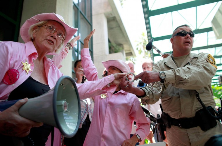 Code Pink protesters interact with law enforcement officers while demonstrating at the Stratz Center for the Performing Arts in Tampa, Florida. The Code Pink protesters were on hand to perform a citizen's arrest on Former Secretary of State Condoleezza Rice for her involvement in the U.S. lead wars in Afghanistan and Iraq. (Tom Pennington/Getty Images)