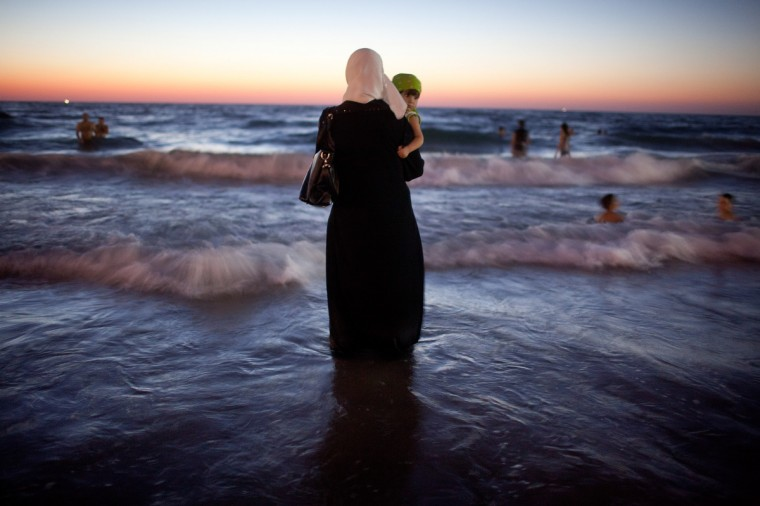 A woman holds her baby as Palestinians enjoy a day at a beach during Eid al-Fitr, which marks the end of the holy month of Ramadan in Tel Aviv, Israel. According to the Israel's coordinator for government activities in the territories, Israel has allowed the entry of over 1 million Palestinians from the occupied West Bank since the beginning of Ramadan due to improved security. (Uriel Sinai/Getty Images)