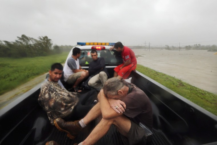 People rest in a rescue truck atop a levee next to floodwaters after being rescued in Plaquemines Parish in Braithwaite, Louisiana. Dozens were reportedly rescued in the area after levees were overtopped by floodwaters from Hurricane Isaac. Today is the seventh anniversary of Hurricane Katrina. (Mario Tama/Getty Images)