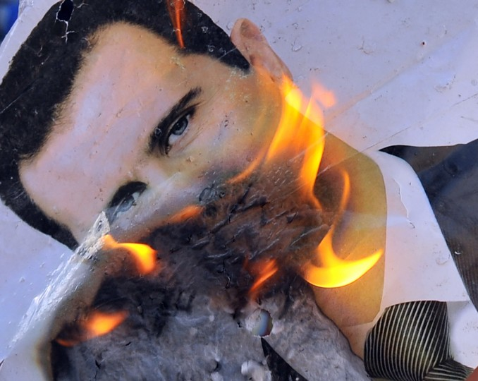 "A portrait of Syrian President Bashar al-Assad burning during clashes between rebels and Syrian troops in the city center of Selehattin, near Aleppo. Syrian rebels ""liberated"" several districts of the northern city of Aleppo on Monday, a Free Syrian Army spokesman in the country's commercial hub said. (Bulent Kilic/GettyImages)"