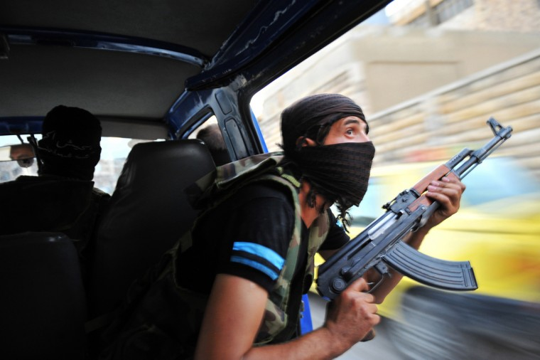"Syrian rebels hunt for snipers after attacking the municipality building in the city center of Selehattin, near Aleppo, on July 23, 2012, during fights between rebels and Syrian troops. Syrian rebels ""liberated"" several districts of the northern city of Aleppo on Monday, a Free Syrian Army spokesman in the country's commercial hub said. Bulent Kilic/GettyImages)"