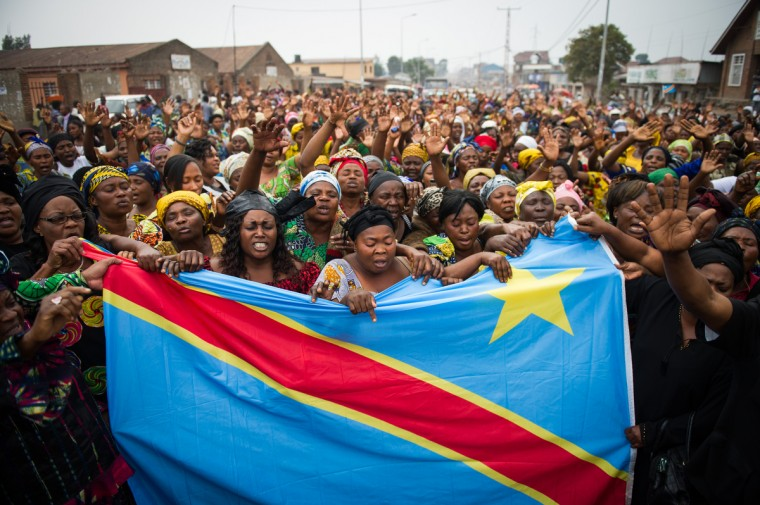 "Congolese women demonstrate for peace in the street outside the Katinde Nazareen church in Goma with a Congolese national flag, following an ecumenical service for peace in the east of the Democratic Republic of the Congo. Civil society and church leaders called people together today, at a Congolese public holiday celebrating parents, to pray for peace, saying their faith is stronger than war. North Kivu province has been wracked by conflict in recent months, as M23 rebels pitch themselves against the Congolese army. ""We will pray until this thing is over"" said one member of the congregation. (Phil Moore/GettyImages)"