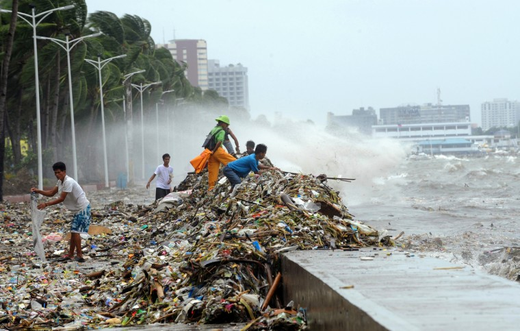 People collect recyclable materials amongst the rubbish washed ashore on Roxas boulevard promenade in Manila, as heavy rains and strong winds brought about by Typhoon Saola hit the capital city for another day. Hundreds of people fled their homes, as Typhoon Saola brought heavy rains, floods and powerful waves to the Philippines, bringing the death toll to 14 after four days of bad weather. (Ted Aljibe/GettyImages)