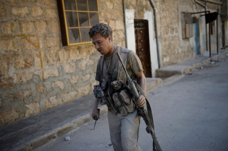 A Syrian rebel covered in plaster dust walks after emerging from a building hit by an army tank shell in the Salaheddin district of the northern city of Aleppo on August 13, 2012. Syrian rebels claimed they downed a fighter jet in what would be a major coup for the opposition but the regime seized the upper hand in Aleppo as it advanced into a new rebel-held district. (Phil Moore/GettyImages)