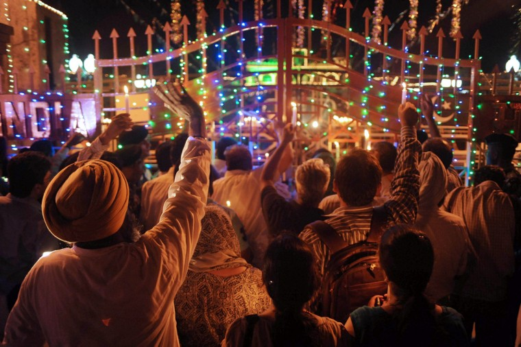 Pakistani and Indian revelers hold up candles and Indo-Pak joint national flags near the border gate during a vigil marking their respective countries' Independence Days at the India-Pakistan border in Wagah late. Pakistan celebrated Independence Day on August 14 and India on the 15th. (Narinder Nanu/GettyImages)