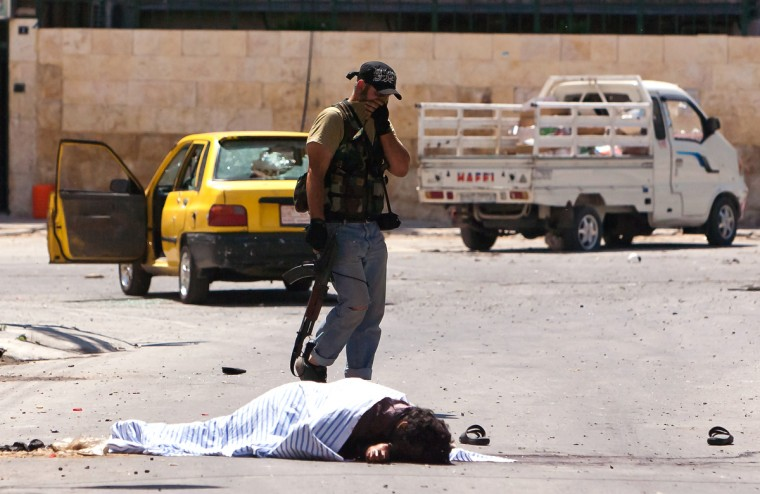 A member of the Syrian opposition walks past a body lying in the street during fighting against forces loyal to President Bashar al-Assad in the disputed neighbourhood of Salaheddin in Syria's northern city of Aleppo on August 13, 2012. Government forces shelled two flashpoint districts of Aleppo and a hospital in the east, which was also hit two days ago, and was largely empty of patients and medical staff, an AFP journalist said. (Vedat Xhymshiti/GettyImages)