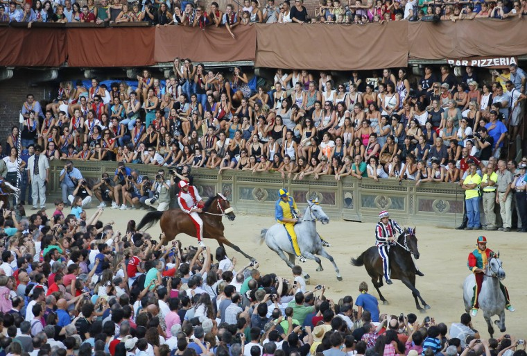 Horses compete during the General Proof on the eve of the Palio horse race, in Siena. The Palio medieval race is held twice a year in Siena with jockeys riding bareback around a makeshift race course set up in the city's central square. (Fabio Muzzi/GettyImages)