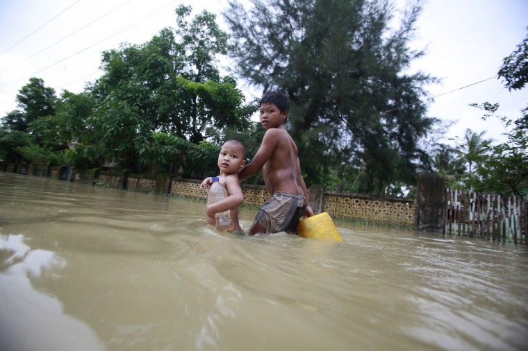 Flood-affected children carrying drinking water in plastic containers past partially-submerged houses in Pathein, in the Irrawaddy delta region of Myanmar. Recent heavy monsoon rains have left swathes of farmland flooded in many parts of central Myanmar. (Ye Aung Thu/GettyImages)