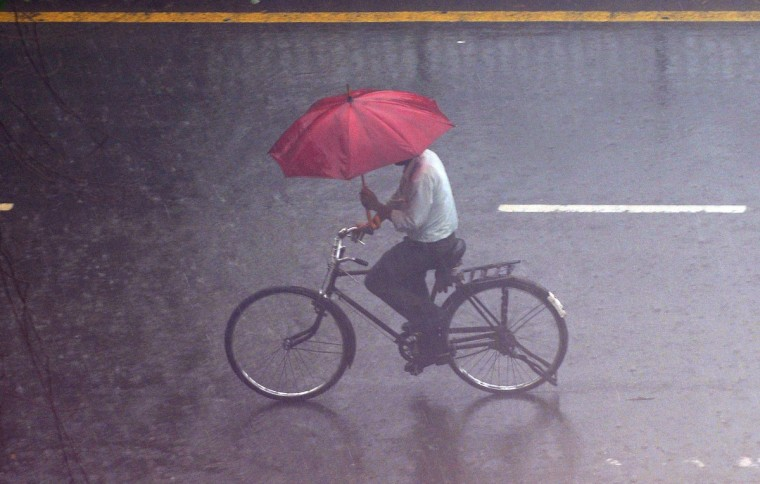A pedestrian cycles with an umbrella as it rains in New Delhi. Nation-wide, the monsoon has been more than 20 percent below its average, sparking fears of drought among farmers who remember vividly the failure of 2009, when India suffered its worst drought in nearly four decades. (Prakash Singh/GettyImages)