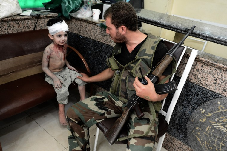 A Free Syrian Army fighter comforts a young wounded boy at a hospital in Syria's northern city of Aleppo, who was injured when a shell, released by regime forces, hit his house. Syrian forces blitzed areas in and around the Aleppo, activists said, as Western powers sought to tighten the screws on embattled President Bashar al-Assad. (Aris Messinis/GettyImages)