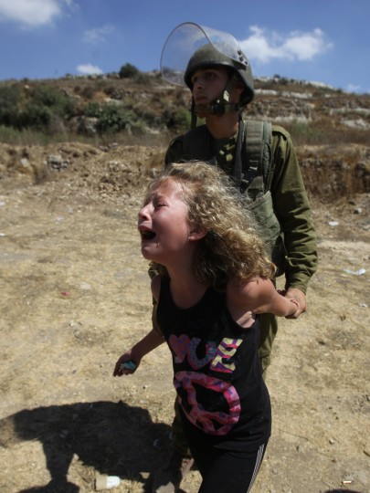 An Israeli soldier holds a Palestinian girl back as she cries following the arrest of her mother during a demonstration in the West Bank village of Nabi Saleh in protest against the confiscation of Palestinian land to expand the nearby Jewish settlement of Halamish . The weekly demonstrations in Nabi Saleh began at the end of 2009, following a years-long legal battle with residents of Halamish settlement who in 2001 seized around 240 acres (100 hectares) of the villagers' land. (Abbas Momani/GettyImages)