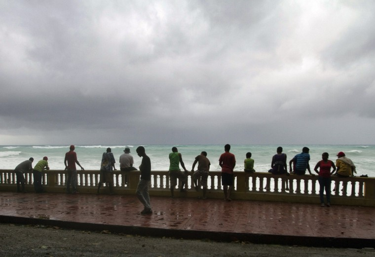 Locals look at high waves caused by Tropical Storm Isaac in Bahoruco, southwest Dominican Republic. Isaac was packing maximum sustained winds of 80 kilometers (50 miles) per hour and moving towards the west at 24 kilometers (15 miles) per hour, the Miami-based US National Hurricane Center (NHC) said. A hurricane watch was in effect for Haiti and a tropical storm watch was in effect for the Dominican Republic. (Erika Santelices/GettyImages)