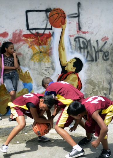 "Children plays basketball next to a graffiti depicting Venezuelan President Hugo Chavez, part of a spontaneous advertising movement ""Chavez es otro Beta"", in Caracas. To support Chavez's re-election, a group of young people called ""Miranda ser otro Beta"" launched a new campaign aimed at youngsters and which attempts to show a youthful Chavez, depicting him in different attitudes. (Leo Ramires/Getty Images)"
